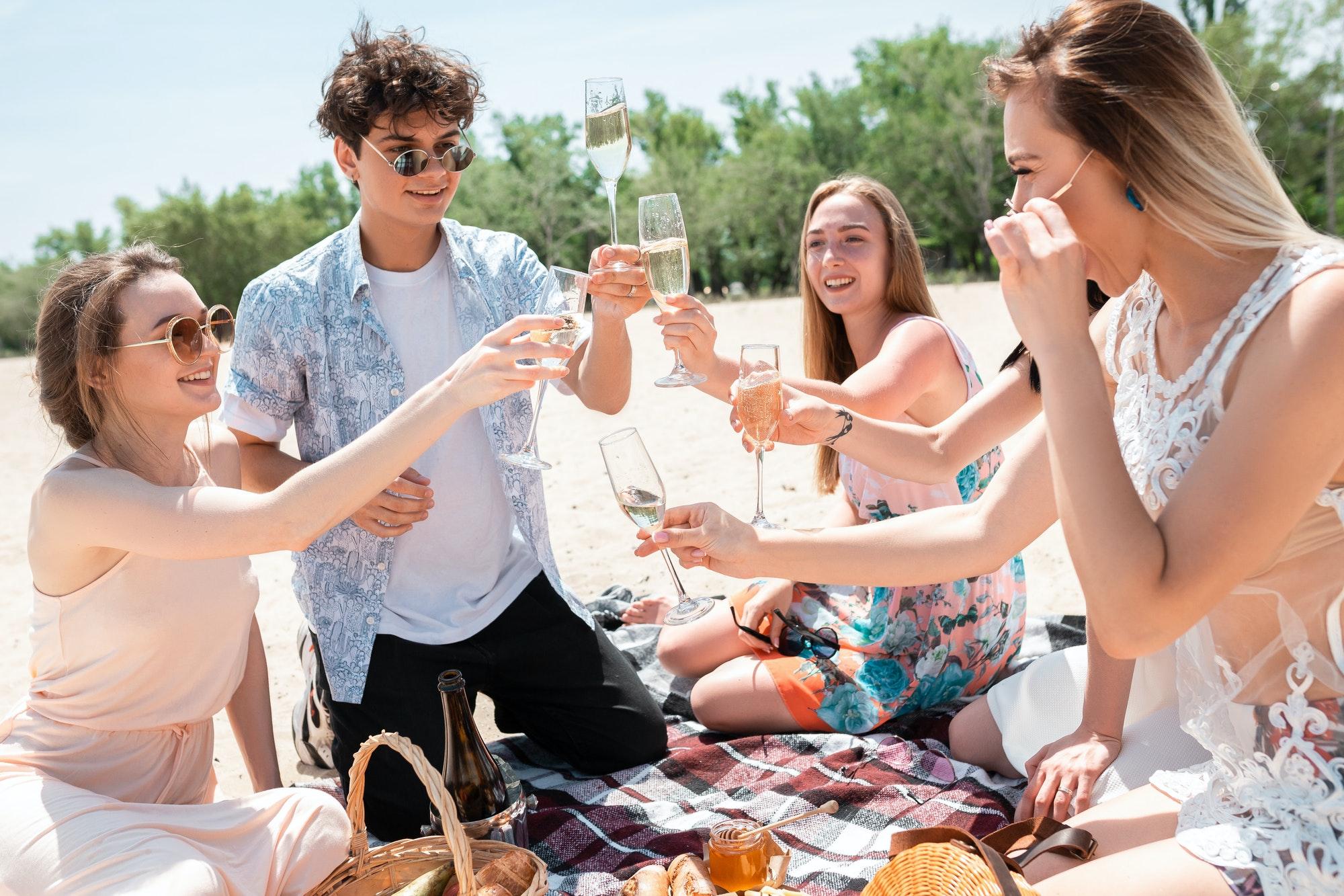 Seasonal feast at beach resort. Group of friends celebrating, resting, having fun on the beach in