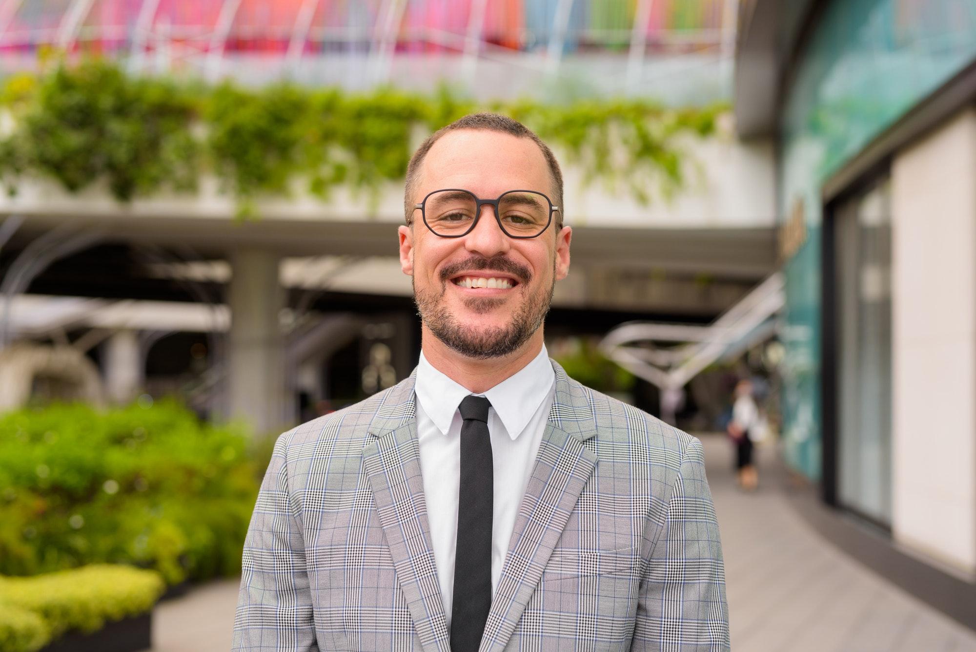 Happy Hispanic bald bearded businessman with eyeglasses smiling outside modern building