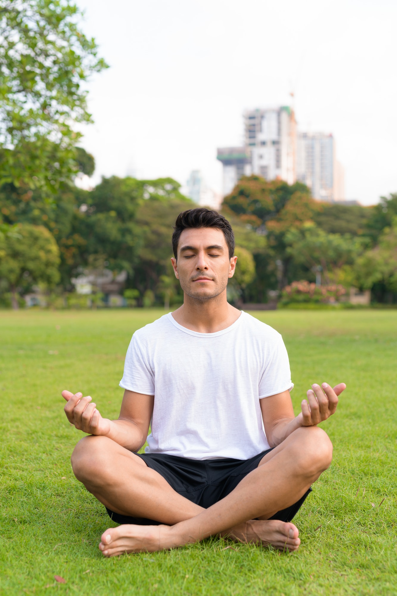 Young handsome Hispanic man meditating at the park outdoors